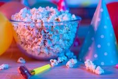 Попкорн с праздничными аксессуарами на предпосылке ТВ Смотрящ ТВ по случаю семейного торжества или в круге  стоковое изображение