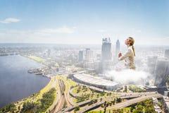 Поплавок женщины над городом стоковая фотография