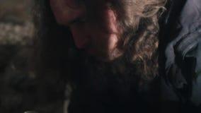 Попрошайка в пакостной, темной комнате ест еду Бездомные образ жизни и потребление наркотиков сток-видео