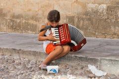 Попрошайка маленького ребенка, играя музыку в улицах Стоковая Фотография