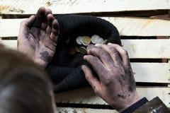 Попрошайка рассматривает монетки Стоковое Фото