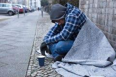 Попрошайка сидя на улице стоковое фото