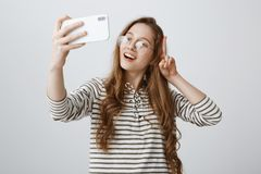 Популярный блоггер моды делает новое vlog используя smartphone Портрет положительной уверенно европейской девушки показывая знак  Стоковые Изображения