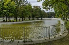 Популярный северный парк для остатков с осенними старыми лесом, деревянной скамьей и цветочным садом в районе Vrabnitsa Стоковые Фото