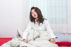 Попытка женщины Азии, который нужно проспать вверх на утре в ее комнате кровати стоковые фото