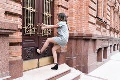 Попытки женщины для того чтобы раскрыть дверь Стоковые Фото