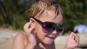Попытки ребенка для того чтобы нести солнечные очки Пляж, солнечный горячий день Стоковое Изображение