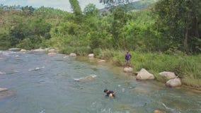 Попытки человека близкого взгляда для того чтобы принять вне сеть от воды среди речных порогов сток-видео