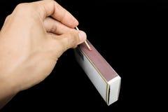 Поражать спичку против коробки спички Стоковые Изображения