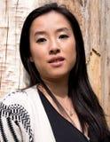 Поразительные азиатские представления девушки закрывают вверх деревом Стоковое Фото