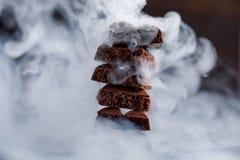 Пористый шоколад в стоге на черном крупном плане предпосылки Части молочного шоколада, выровнянные вверх в башне, положенной в ко Стоковая Фотография