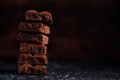 Пористый шоколад в стоге на черном крупном плане предпосылки Части шоколада молока пористого, лежа na górze одина другого Место в Стоковые Фото