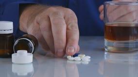 Порочный алкоголь комбайна человека и медицинские таблетки стоковая фотография