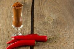 Порошок перца Chili и chili в малом стекле Стоковая Фотография