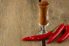 Порошок перца Chili и chili в малом стекле Стоковые Фото