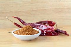 Порошок Chili и высушенный chili на деревянной предпосылке, приправляя Стоковое Изображение
