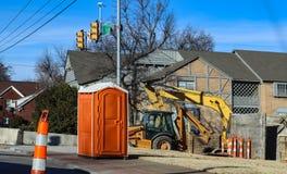 Портативная ванная комната на строительной площадке на intersectio городских дорог с backhoe в конусах предпосылки и движения вок стоковые фото