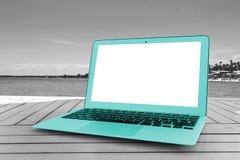 Портативный компьютер бирюзы на деревянном столе Передний вид на океан остров предпосылки тропический Раскройте космос пустого по Стоковые Изображения RF