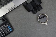 Портативный компьютер или тетрадь и бинокулярное, калькулятор и чашка  Стоковое Изображение