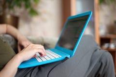 Портативный компьютер лежит на коленях и руках работая на своей клавиатуре Стоковые Фото