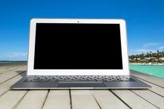 Портативный компьютер на деревянном столе Верхний вид на океан остров предпосылки тропический Раскройте космос пустого портативно стоковые фотографии rf