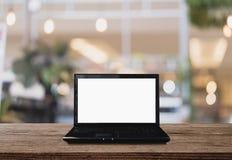 Портативный компьютер на деревянном столе в кафе, Bokeh освещает предпосылку Стоковые Фото