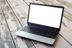 Портативный компьютер на деревянном поле с пустым экраном стоковое фото