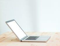 Портативный компьютер пустого экрана на деревянной таблице Стоковые Изображения
