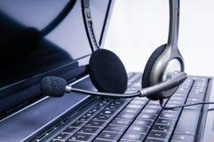 Портативный компьютер с шлемофоном на клавиатуре стоковое изображение