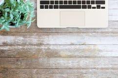 Портативный компьютер таблицы стола офиса и свежий цветок на деревянных животиках Стоковые Изображения