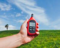 Портативный термометр в руке измеряя внешние температуру воздушной среды и влажность стоковое изображение rf