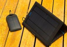 2 портативных солнечных заряжателя сидя на деревянной поверхности, современная зеленая концепция технологии, Стоковое Фото