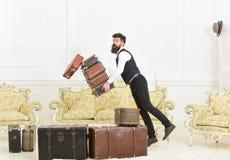 Портер, дворецкий случайно споткнулся, падающ куча винтажных чемоданов Концепция страхования багажа Человек с бородой и стоковое фото rf