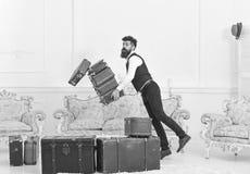 Портер, дворецкий случайно споткнулся, падающ куча винтажных чемоданов Концепция страхования багажа Человек с бородой и стоковые изображения rf