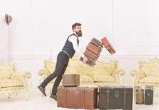 Портер, дворецкий случайно споткнулся, падающ куча винтажных чемоданов Концепция страхования багажа Человек с бородой и стоковая фотография rf