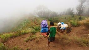 Портер идя вниз от горы Rinjani, Lombok, Индонезии Стоковое фото RF