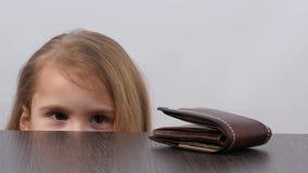 Портмоне на таблице Взгляды девушки в сторону и принимают бумажник акции видеоматериалы