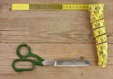 портновский метр и ножницы на деревянной предпосылке стоковые фото