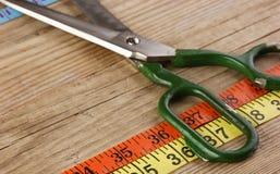 портновский метр и ножницы на деревянной предпосылке стоковые изображения rf