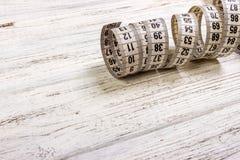 портновский метр и ножницы на старой деревянной предпосылке стоковые изображения