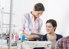 Портнои женщины используя таблетку цифров в фабрике Стоковые Изображения RF