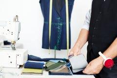 Портной выбирая ткань в Atelier стоковые изображения