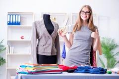 Портной молодой женщины работая в мастерской на новом платье Стоковое фото RF