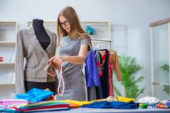 Портной молодой женщины работая в мастерской на новом платье Стоковая Фотография