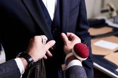 Портной прикалывая изготовленный на заказ костюм Стоковое Фото