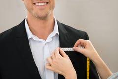 Портной принимая измерение пальто стоковые фотографии rf