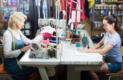 2 портноя женщин работая с швейными машинами Стоковые Изображения