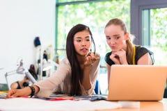 Портняжничайте женщин или модельеры работают на проекте на тетради Стоковая Фотография RF