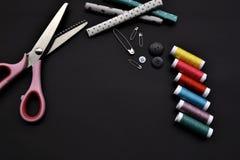Портняжничайте материалы и украсьте дырочками пару ножниц на черной предпосылке стоковая фотография rf