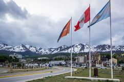 Портовый район Ushuaia, с флагом Аргентины и снежными горами Стоковые Изображения